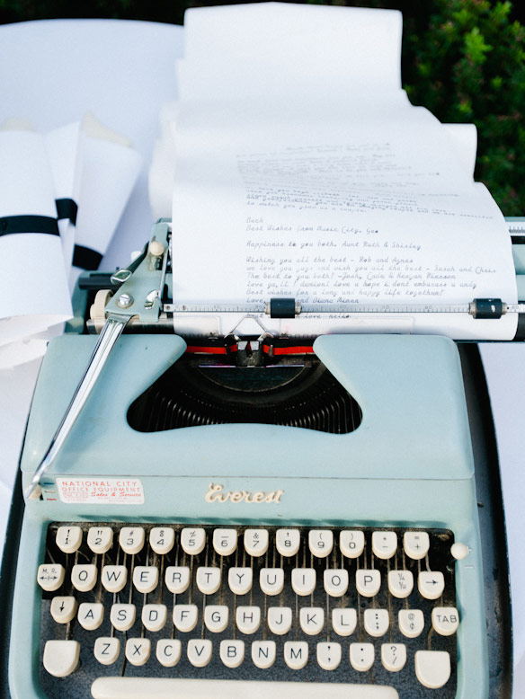 blue vintage typewriter with scroll paper with notes from guests