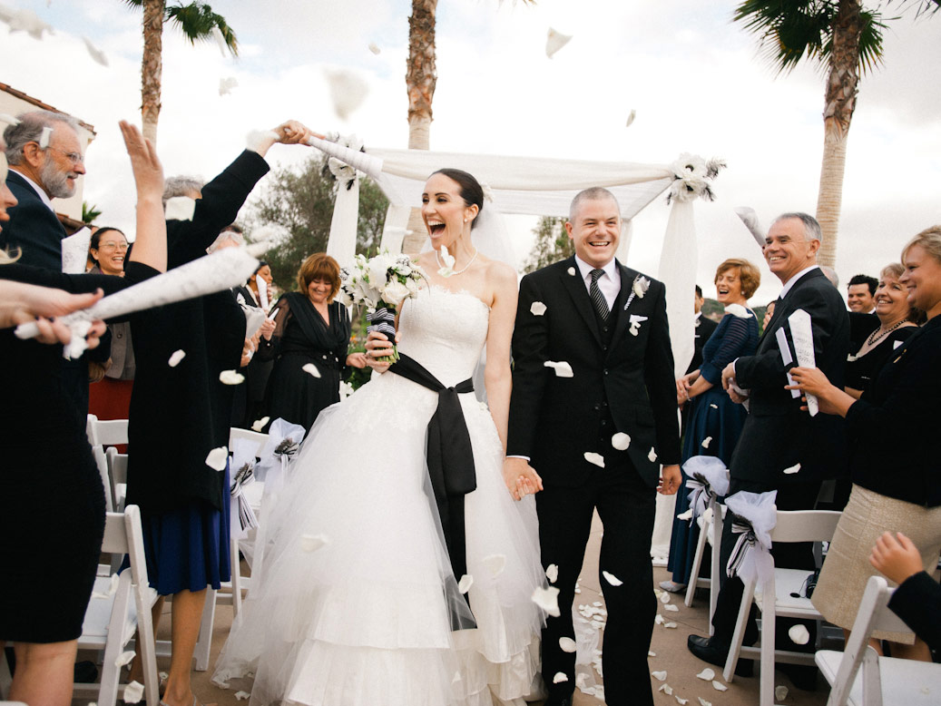 wedding guests toss white rose petals bride and groom walk down after ceremony in rancho santa fe