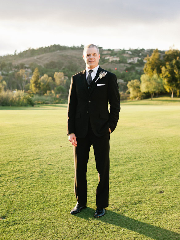 groom in tuxedo stands on golf course at crosby club wedding