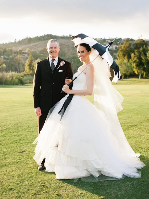 bride holding black and white parasol poses with groom crosby club wedding