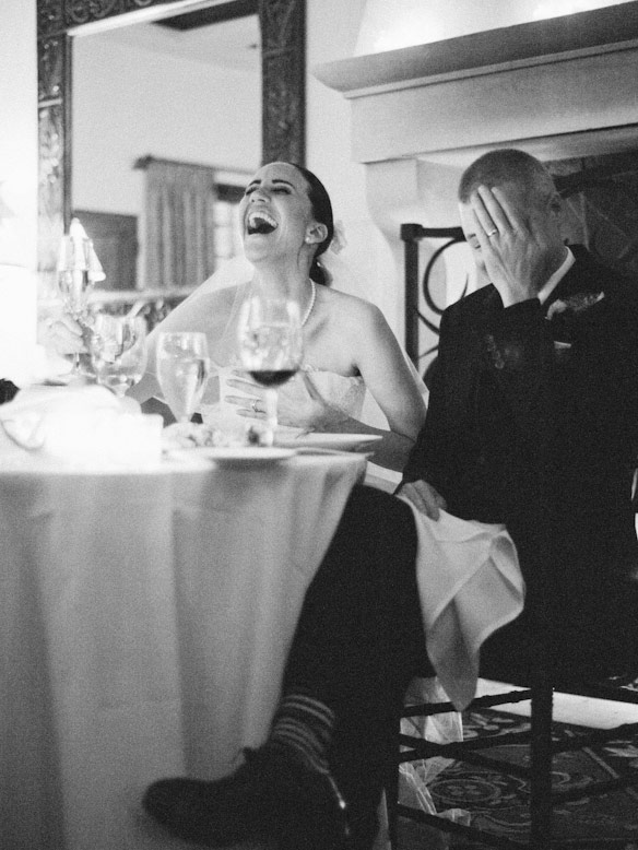bride laughs and groom puts palm to face as toasts are read during wedding reception