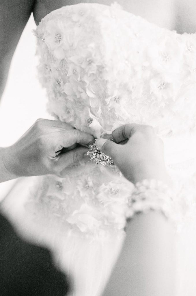 bridesmaid-attaches-brooch-designer-gown-laughton-estate-wedding