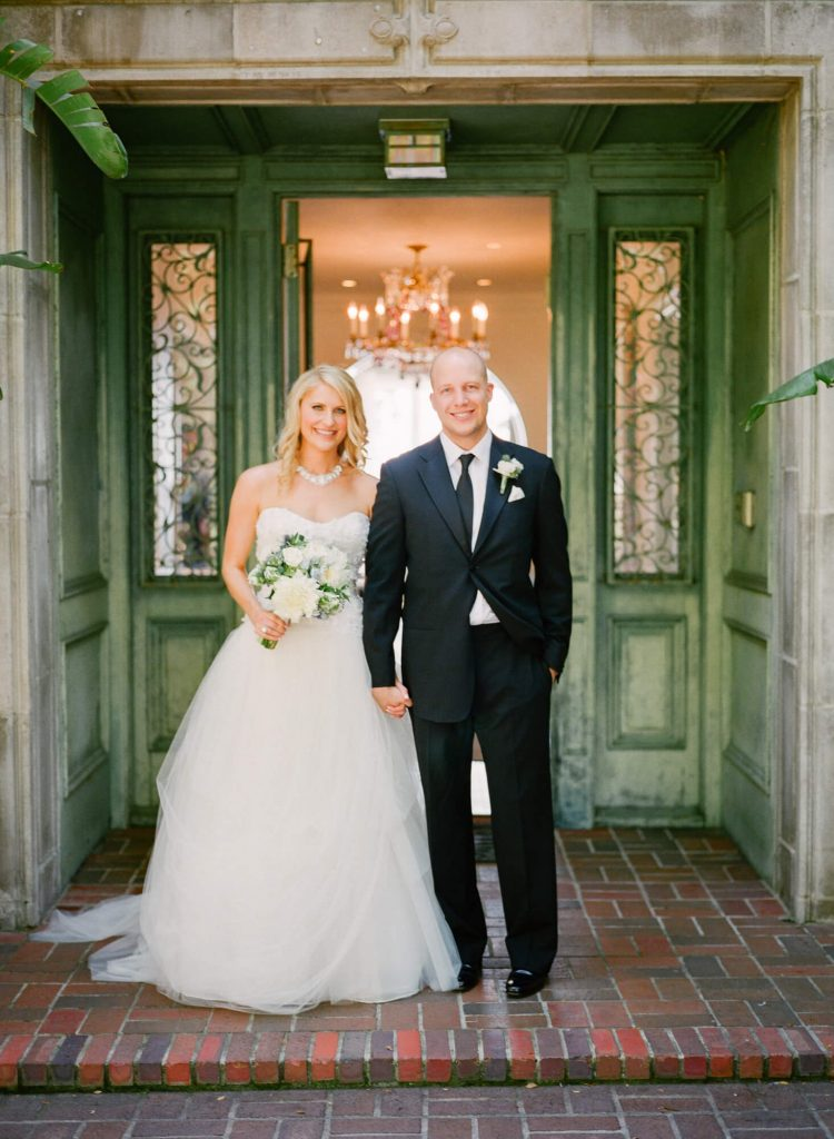bride and groom pose in front of door to laughton estate