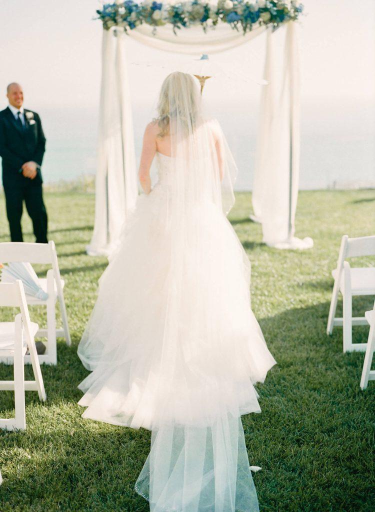 bride walks with parasol toward wedding arch at laughton estate