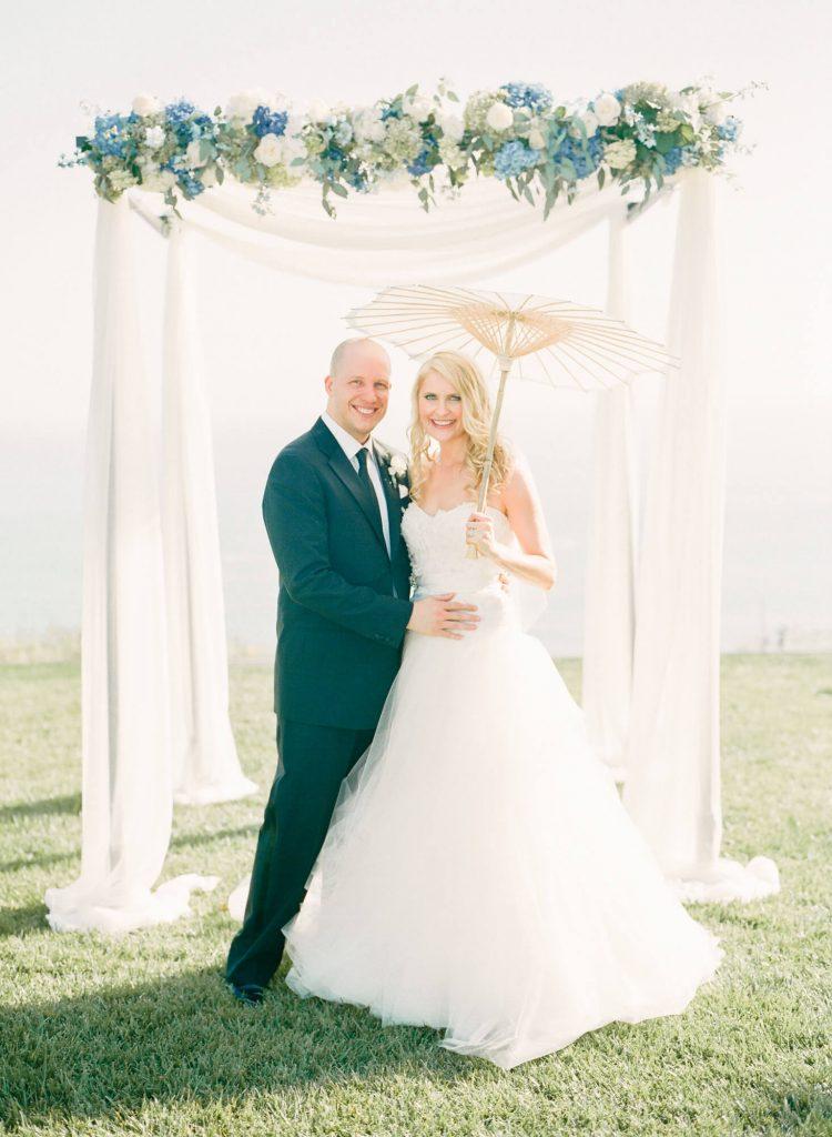 bride and groom pose under wedding arch at laughton estate