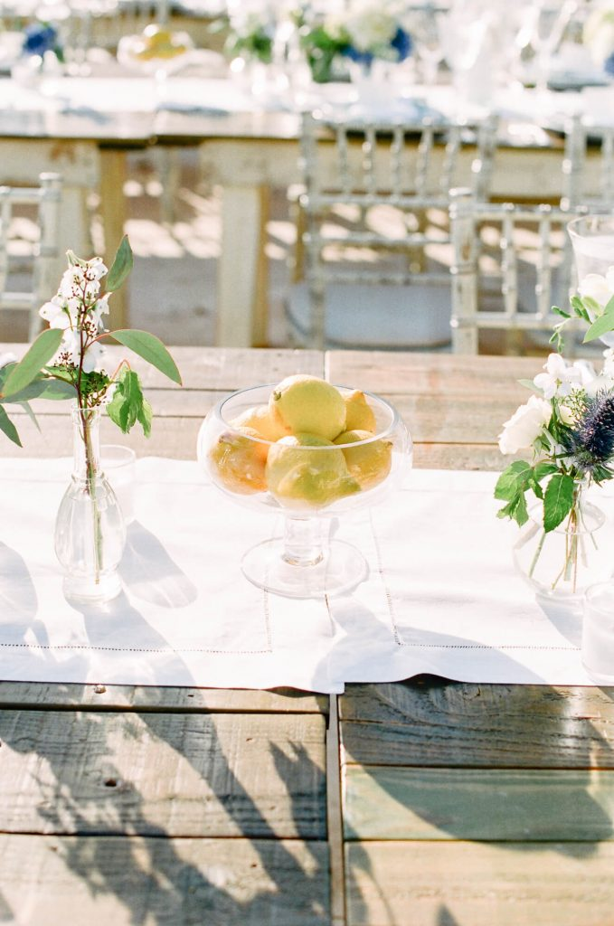 bowl of lemons and bright floral centerpieces on long wooden table for laughton estate wedding