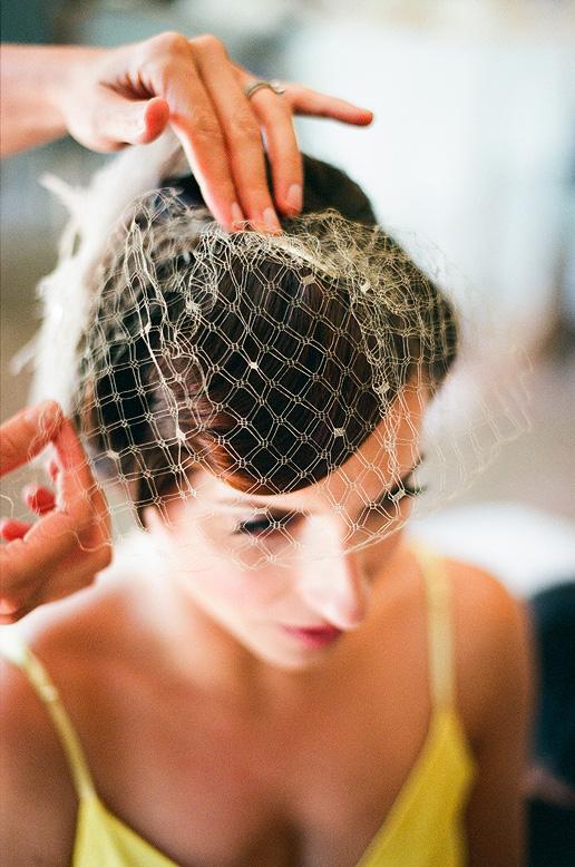 bride putting on birdcage veil