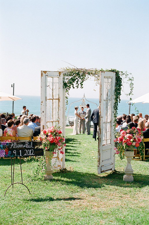 bride and groom standing at altar through vintage doors