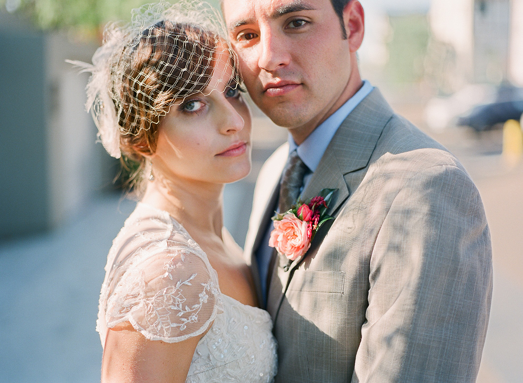 bride wearing vintage dress and birdcage veil poses with groom in gray suit after l'auberge del mar wedding