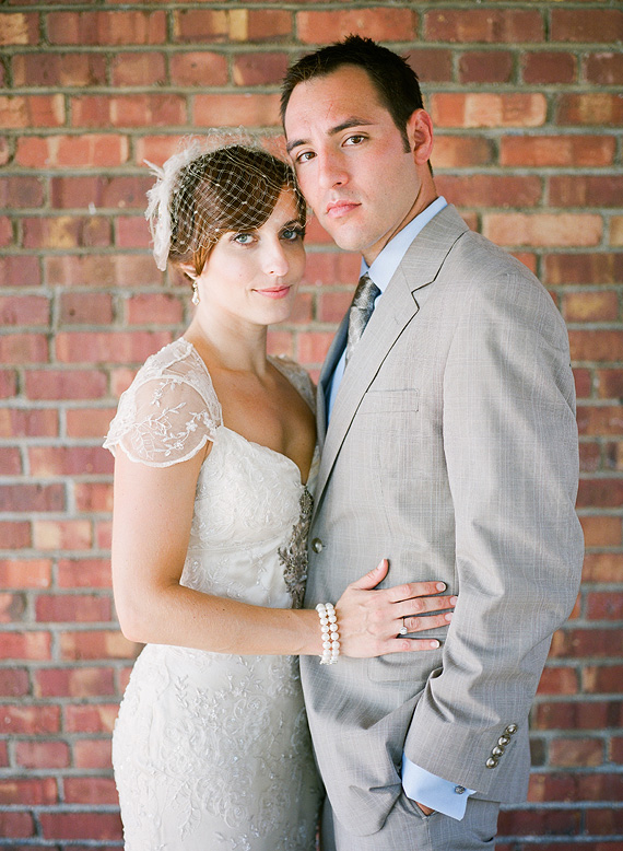 bride wearing vintage dress and groom wearing tan suit pose in front of red brick wall