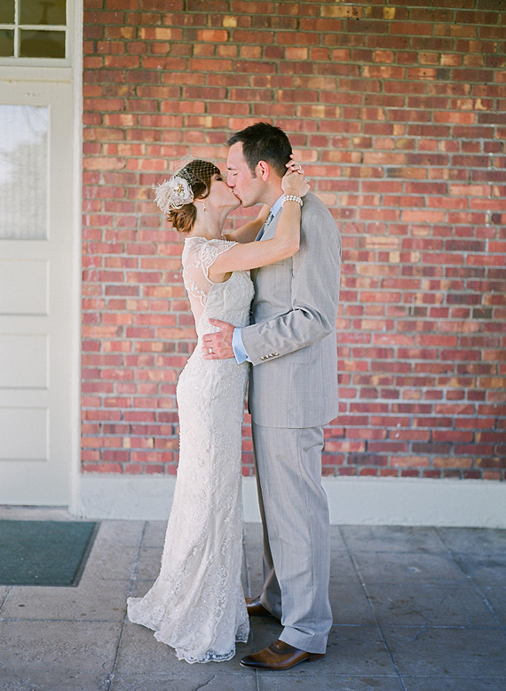 vintage bride and groom kissing in front of red brick wall