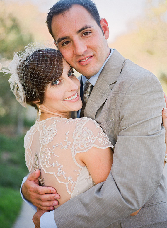 bride wearing vintage dress and birdcage veil poses with husband in tan suit