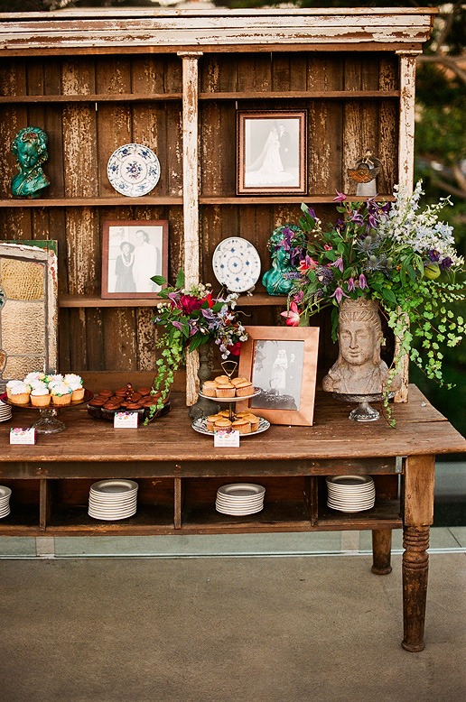 vintage wooden table and hutch holding desserts and picture frames
