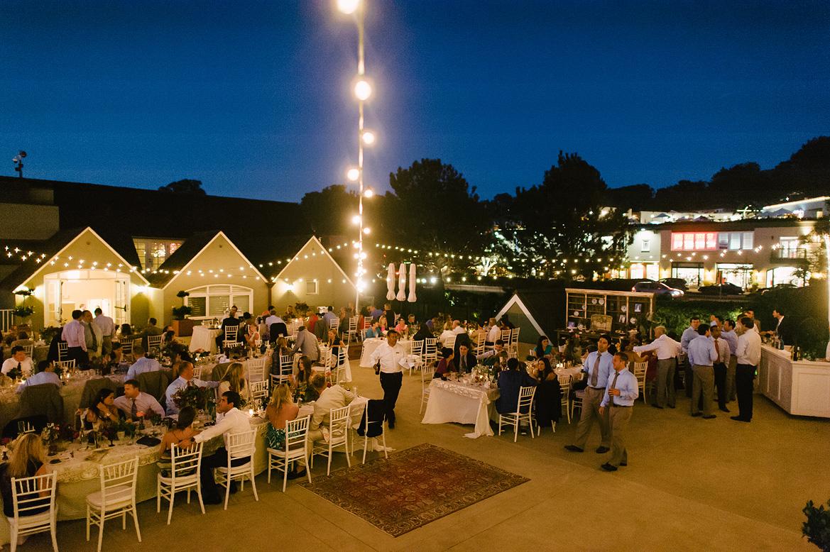 guests dine under market lights at dusk on sunset terrace during l'auberge del mar wedding reception