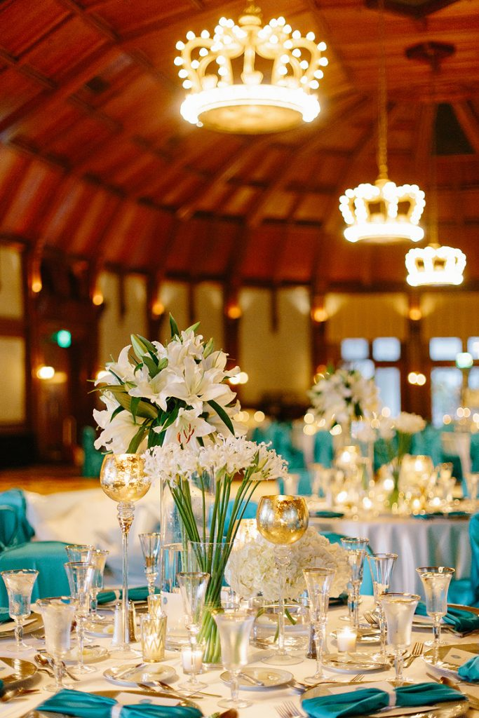 centerpieces of white lilies and blue linens in crown room wedding reception