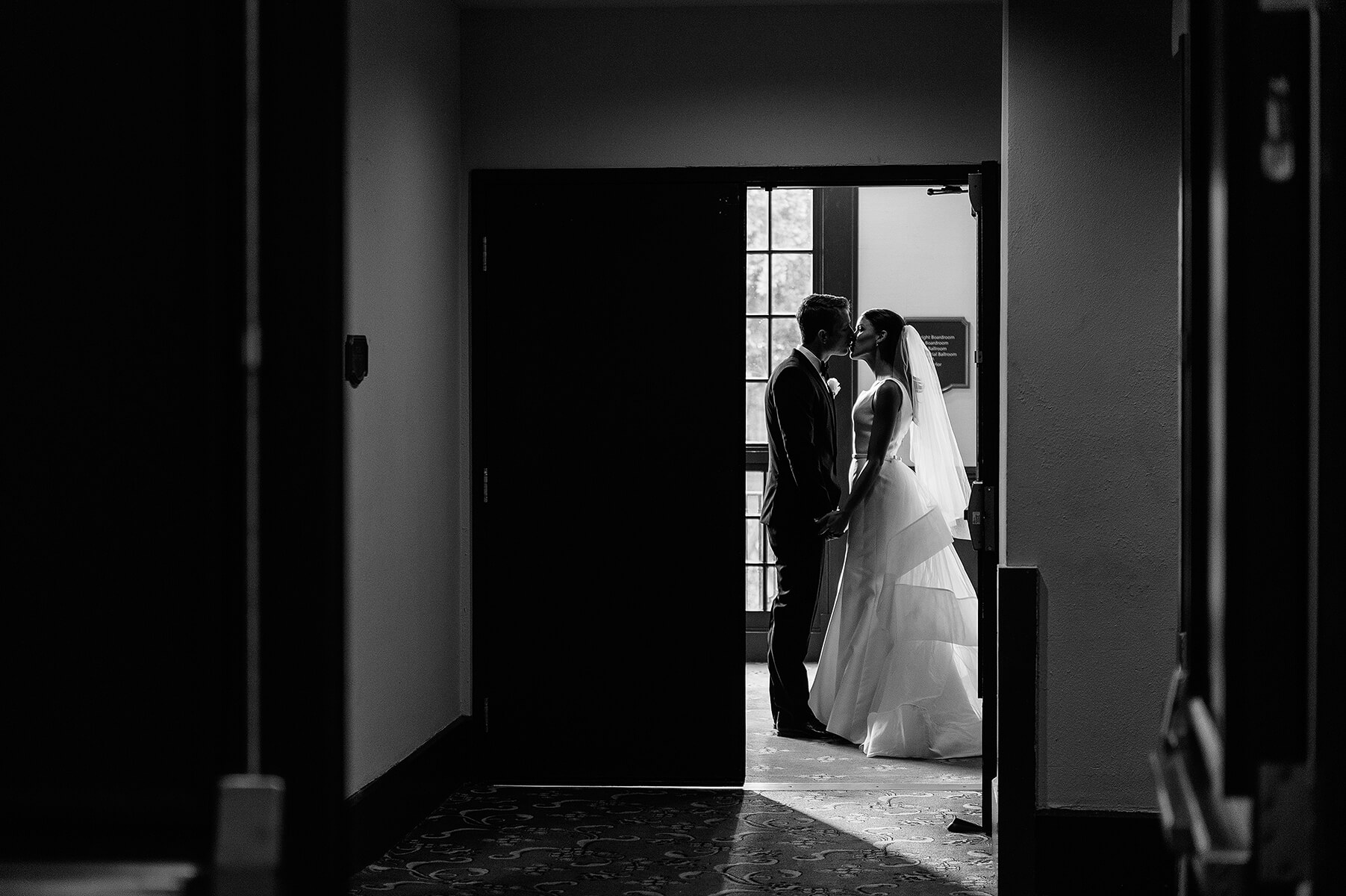 bride and groom sneak kiss in hallway at us grant hotel