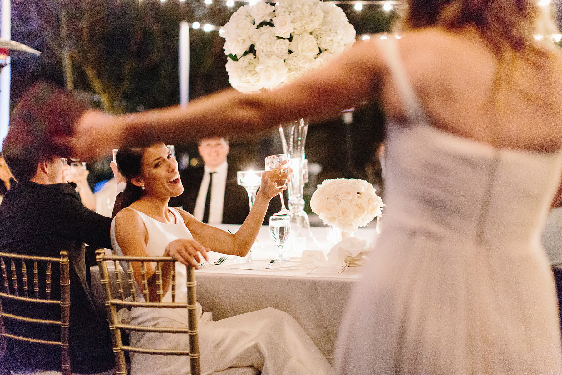 bride raises glass to toast bridesmaid after speech