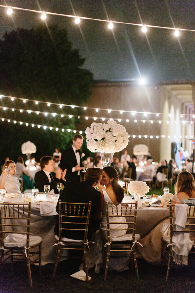 bride and groom kiss at head table at san diego museum of art wedding