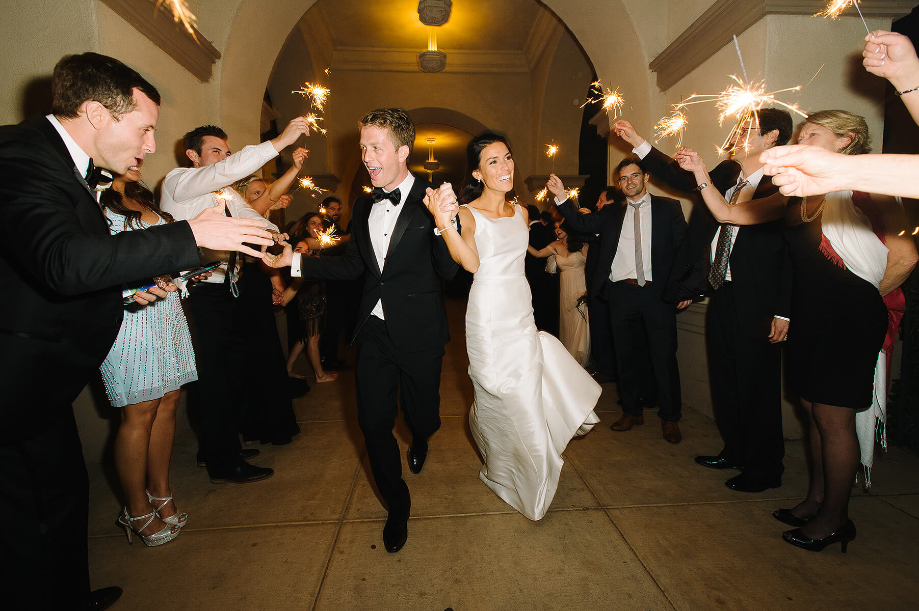 bride and groom run through sparkler exit at balboa park