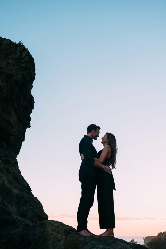 couple posing on rocks el matador beach engagement photo
