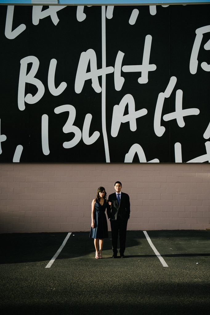 couple posing in front of mural la jolla engagement photo