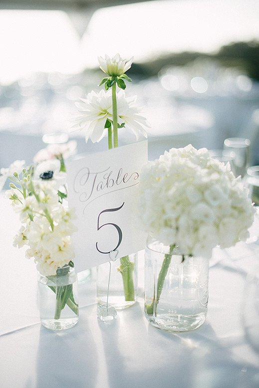 table number and white flowers glass vases wedding decor