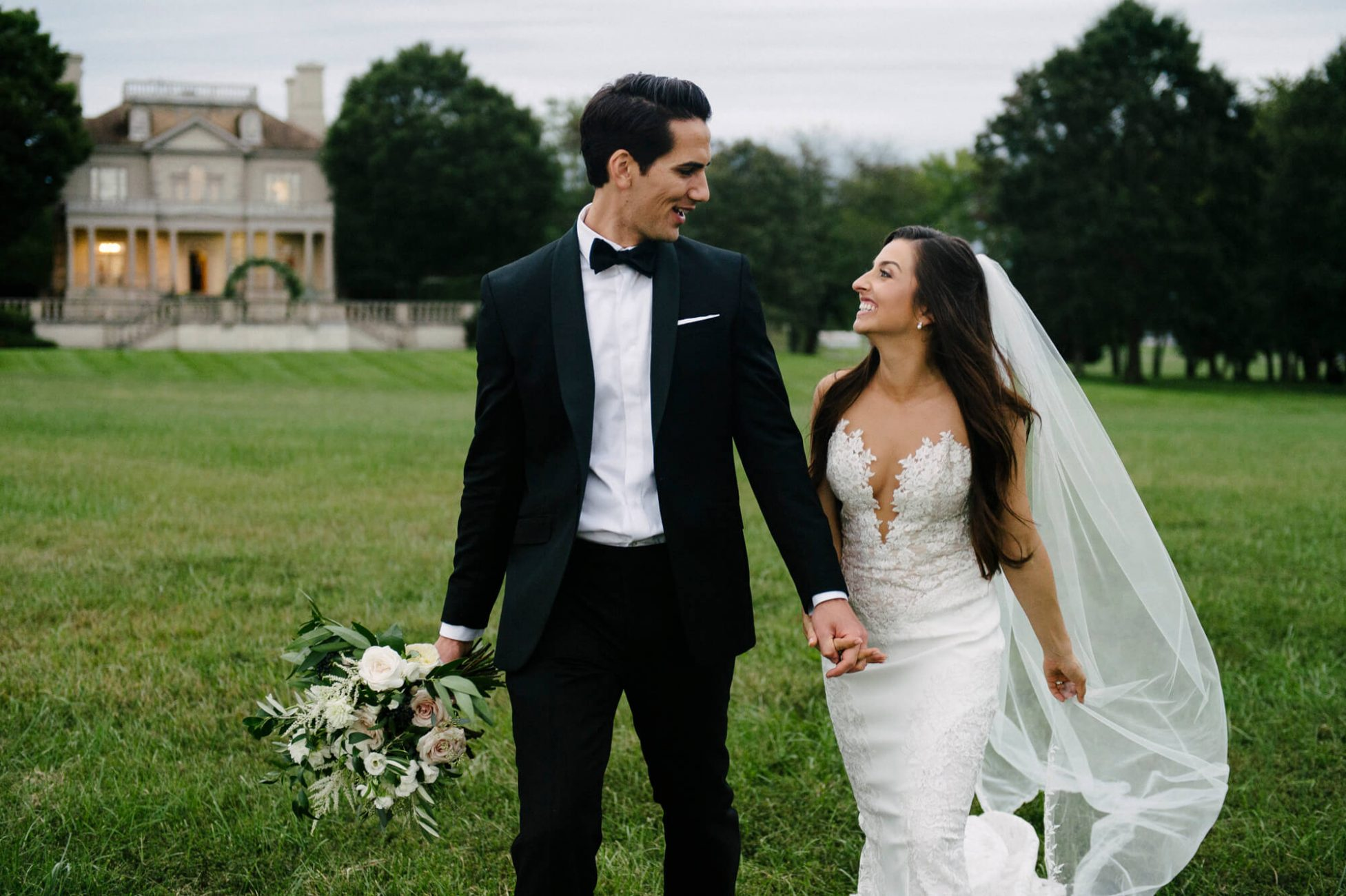 Husband and wife stroll the grounds of Great Marsh Estate after their classic destination wedding.