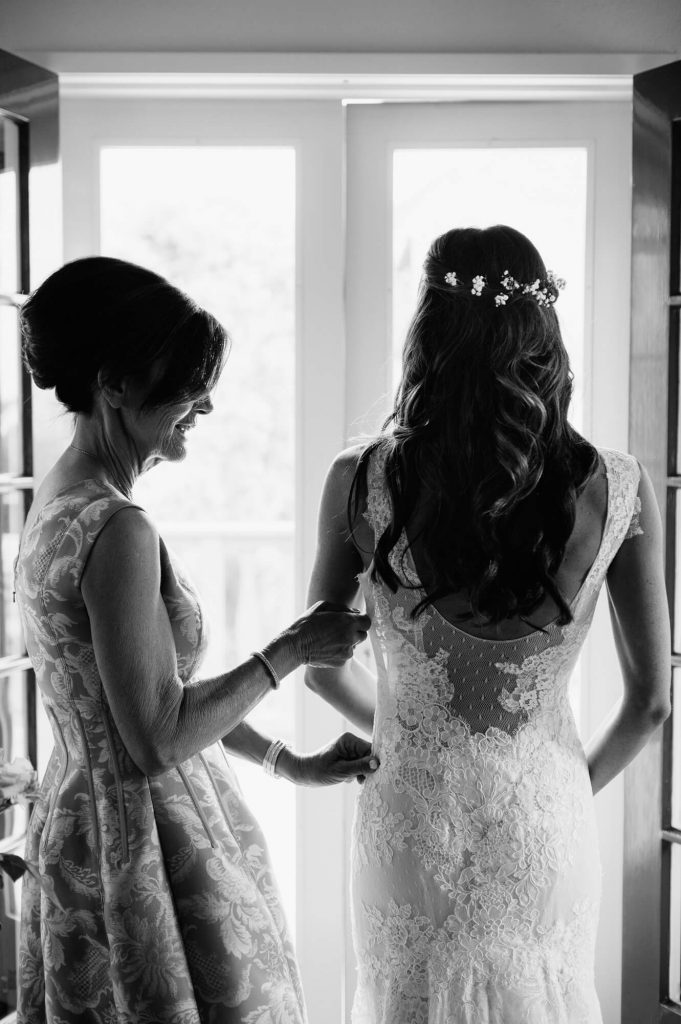 brides mother helping daughter into wedding gown