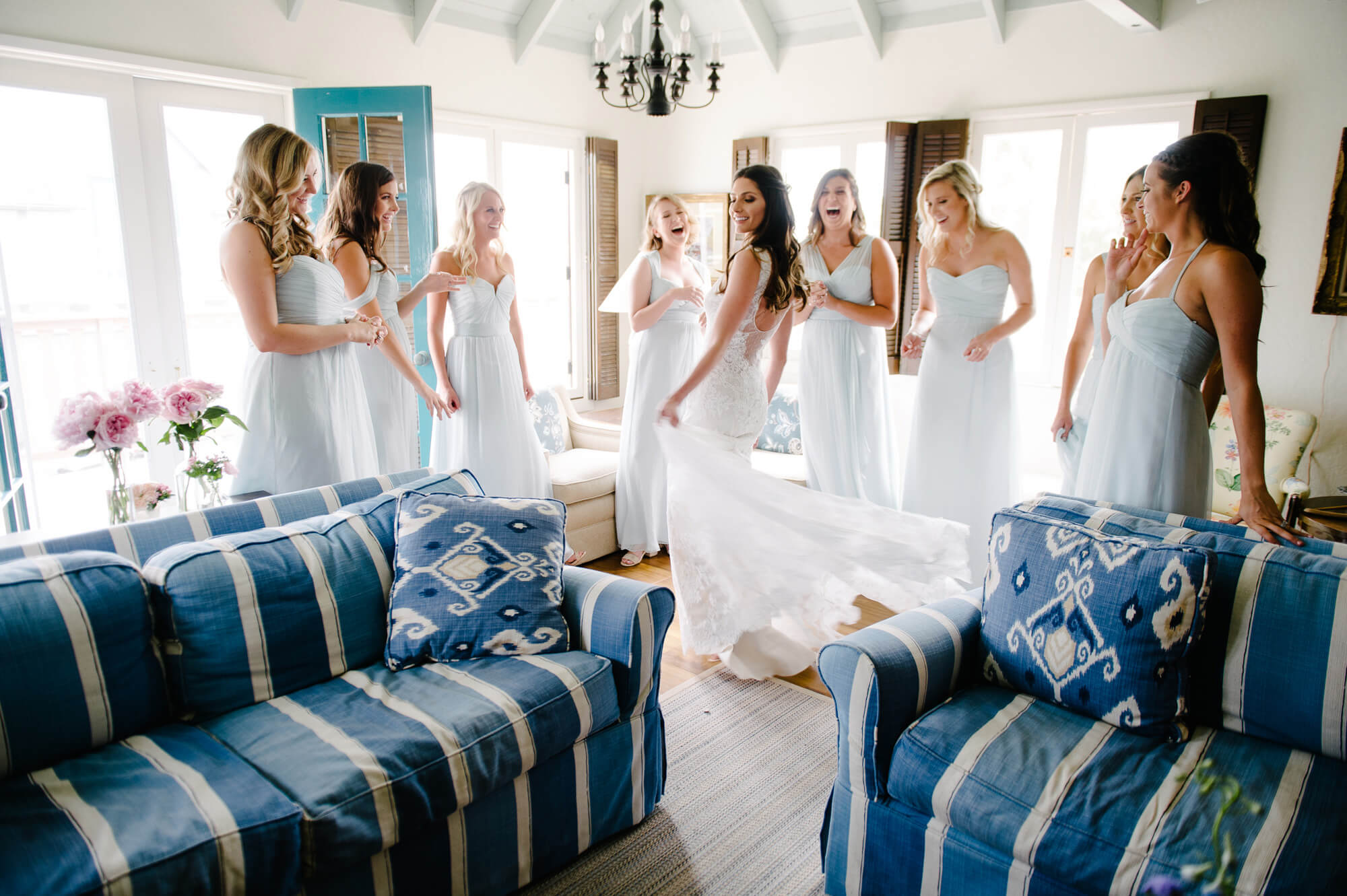 bride shows off gown in front of bridesmaids wearing light blue dresses before st malo beach wedding