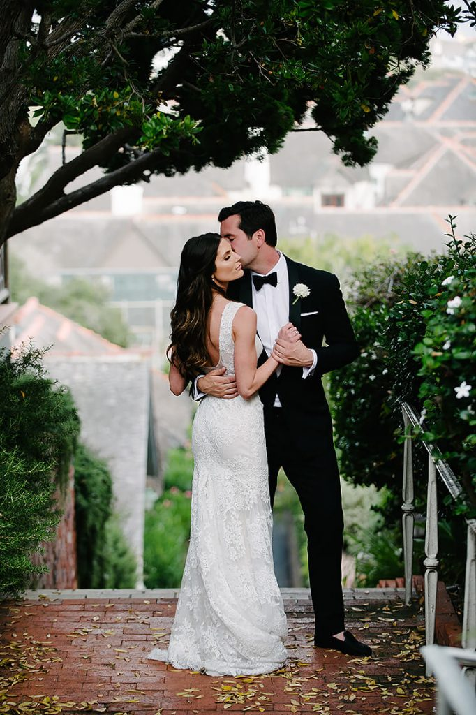 bride and groom kissing brick steps st malo beach wedding