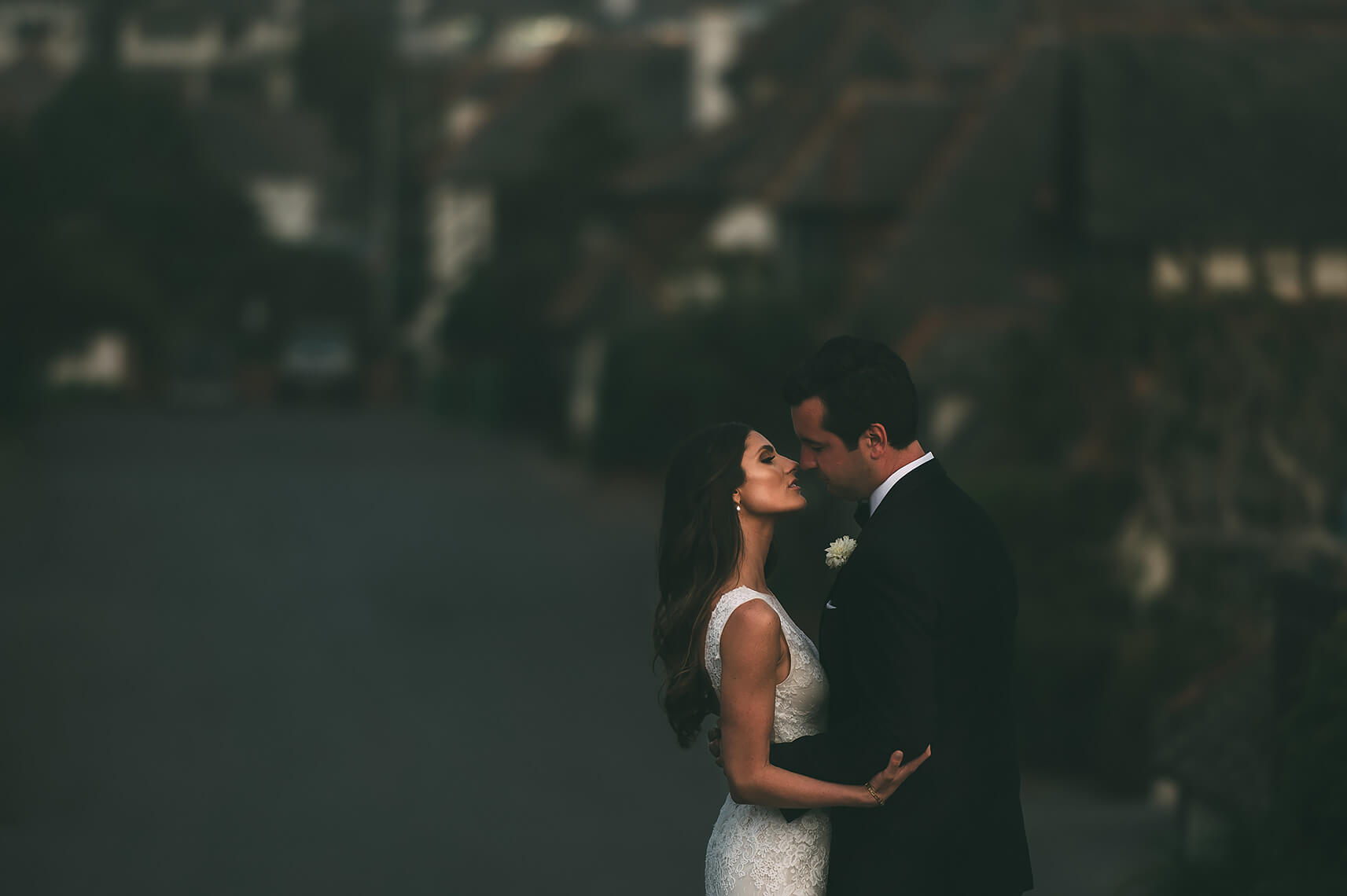 Bride and groom share a kiss after their classic beach wedding in Oceanside, California.