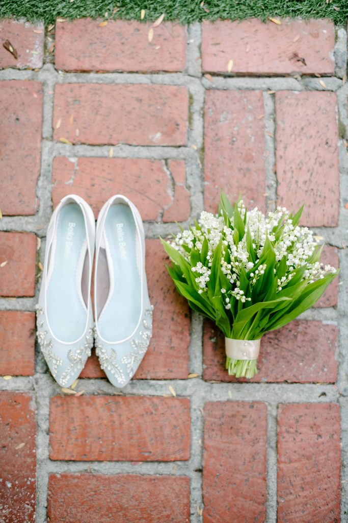 bella belle willow bridal flats with lily of the valley bouquet on red brick