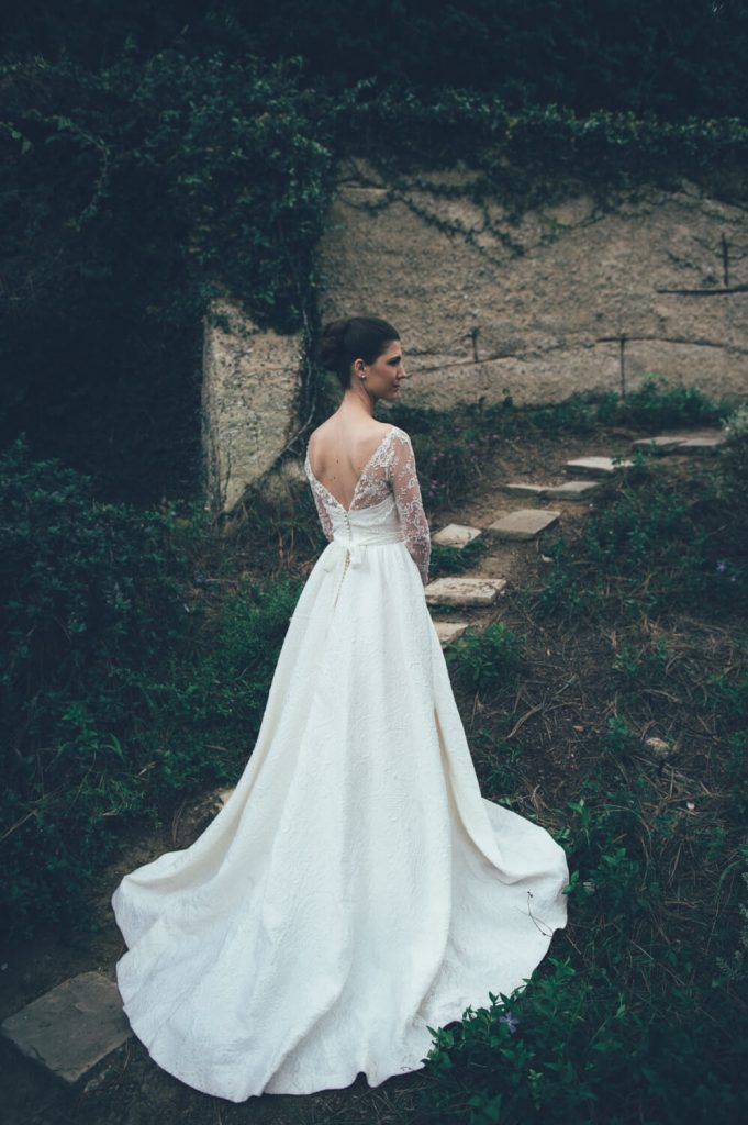 bride in gown with long train and lace sleeves in english garden for la jolla bridal portrait