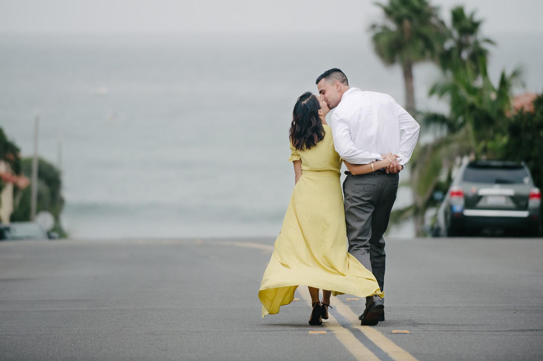couple kiss walking down marine street in la jolla engagement photo