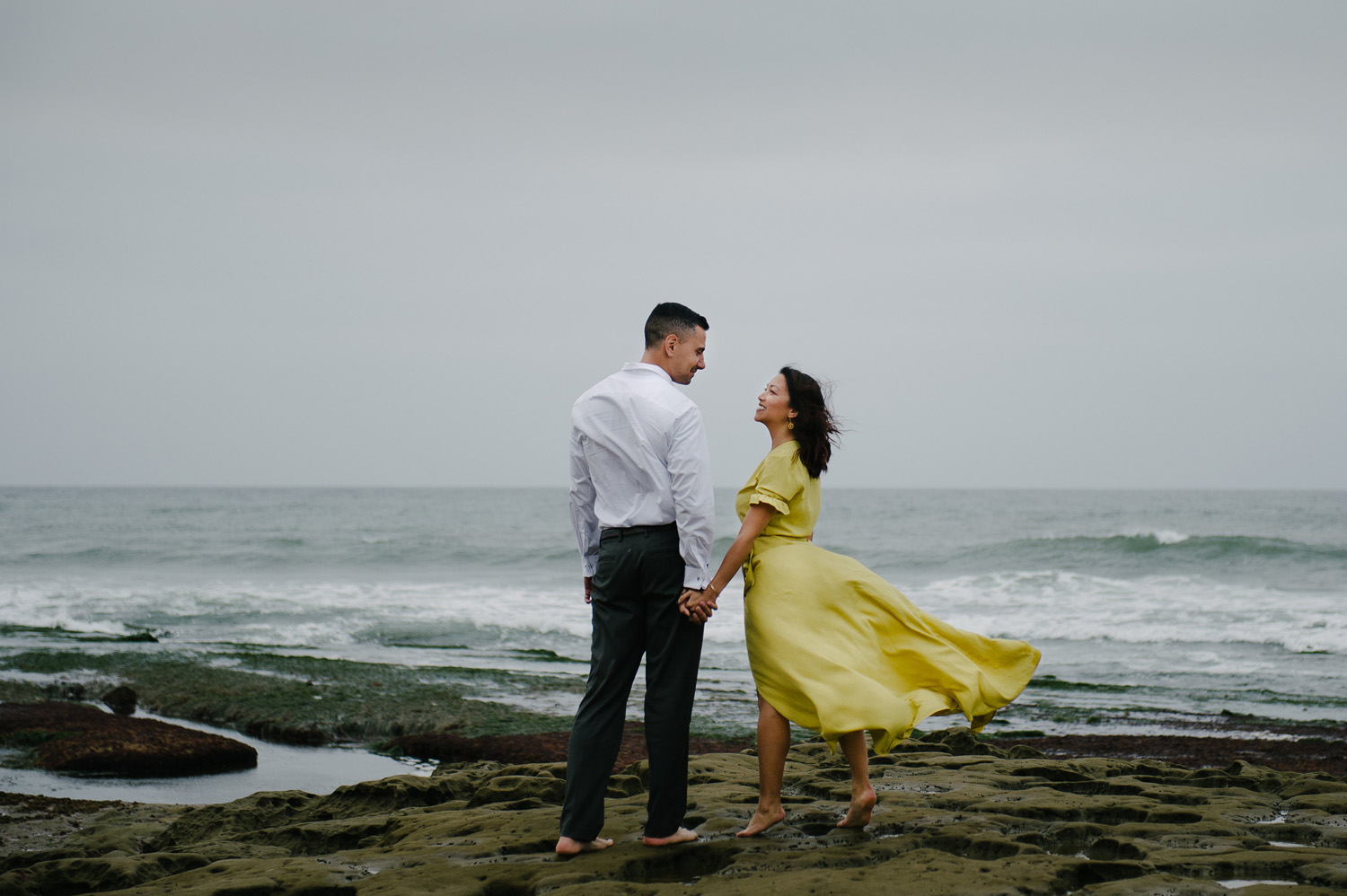 wind blows woman's yellow dress while holding hands with fiancee on marine street beach engagement shoot