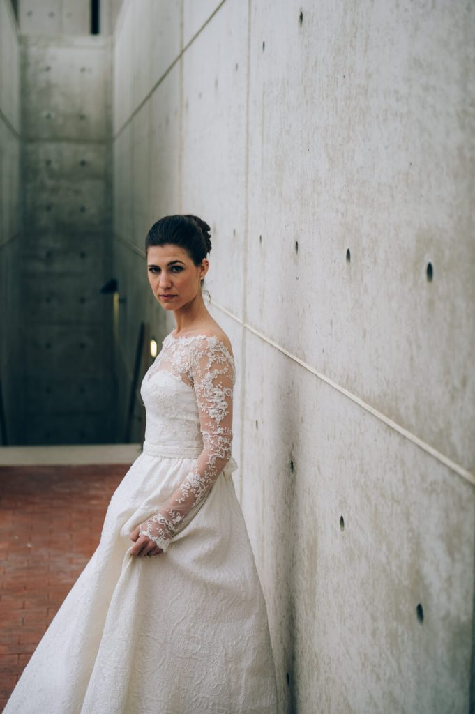 bride in gown with long train and lace sleeves poses at salk institute la jolla bridal portrait