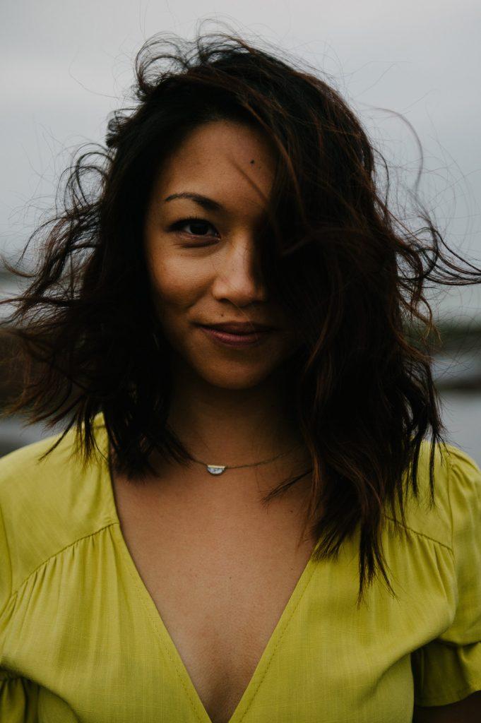woman in yellow dress with windblown hair on la jolla beach