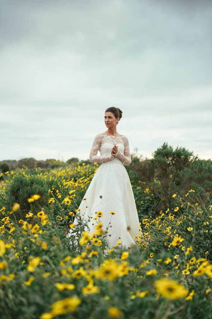 bride in gown with long train and lace sleeves poses at scripps coastal reserve
