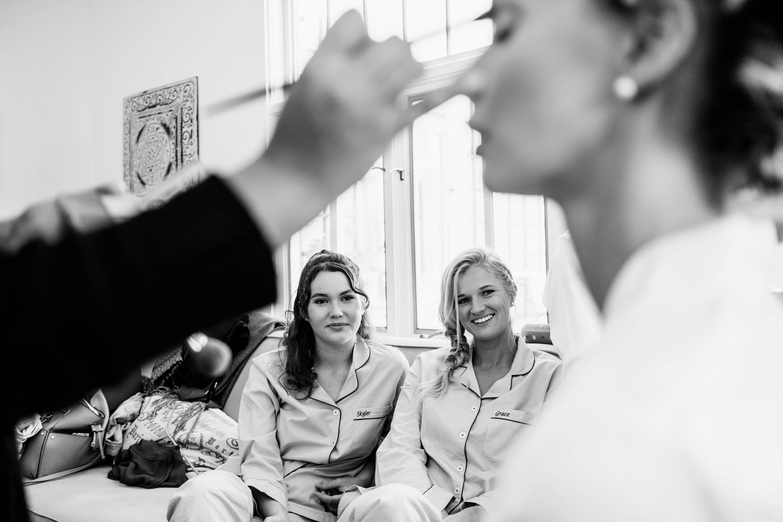 bridesmaids watch bride get makeup applied in matching pajamas