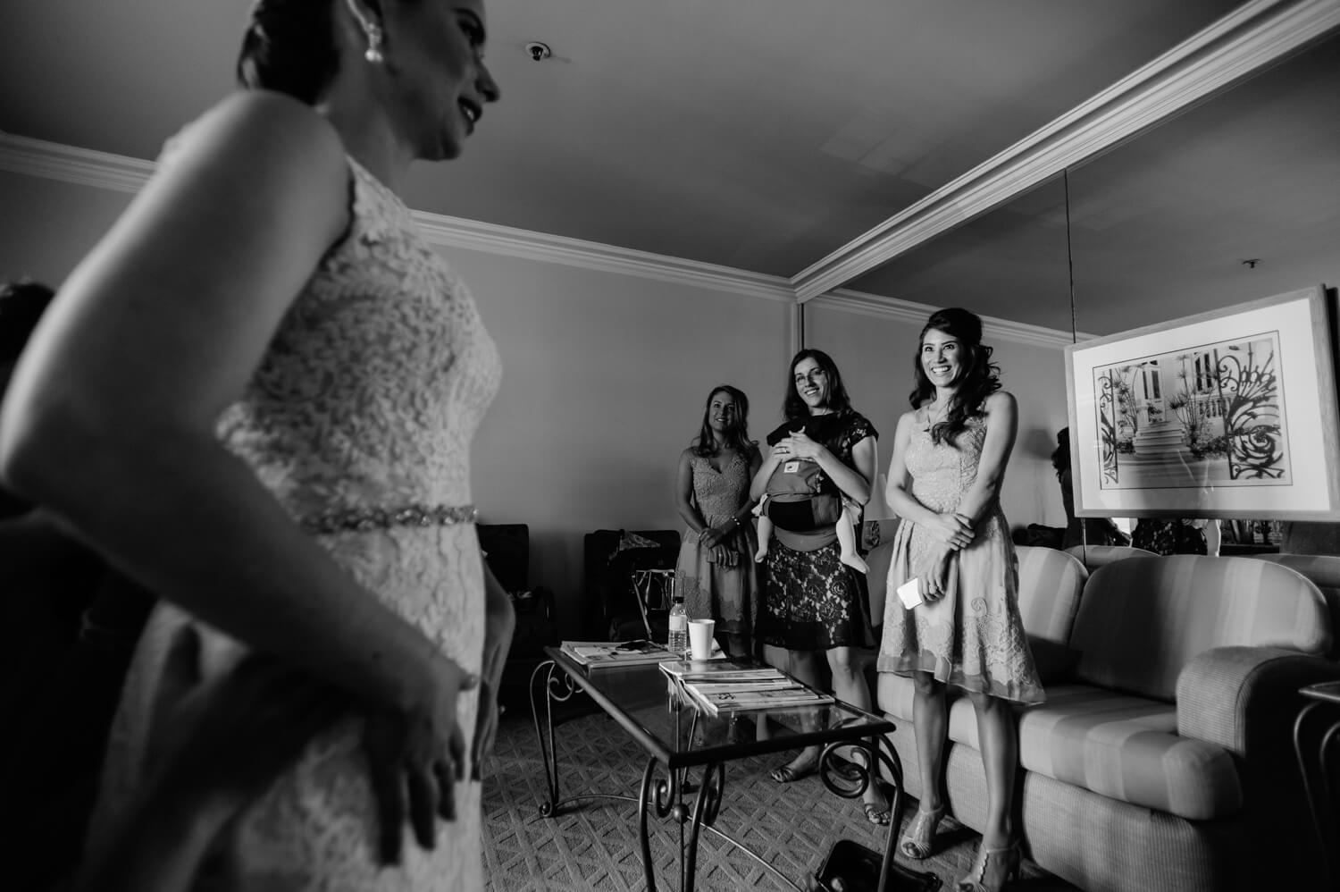 bridesmaids smile as bride looks in mirror to put finishing touches on gown before all hallows wedding