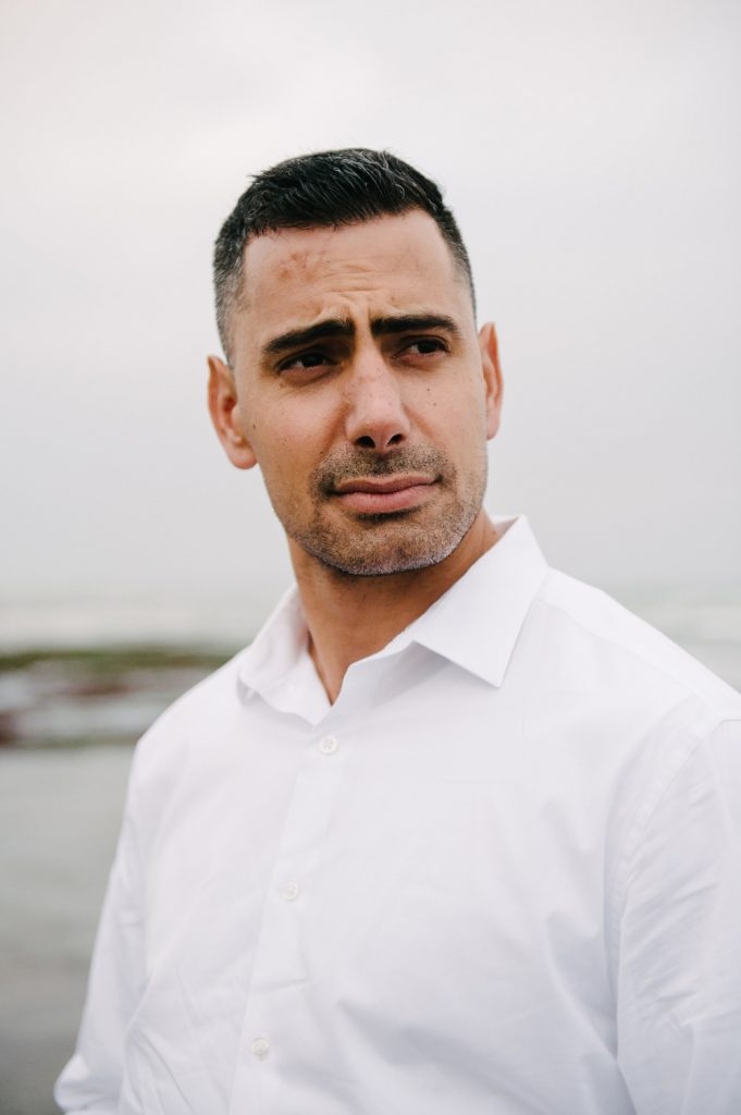 man in white dress shirt poses on la jolla beach