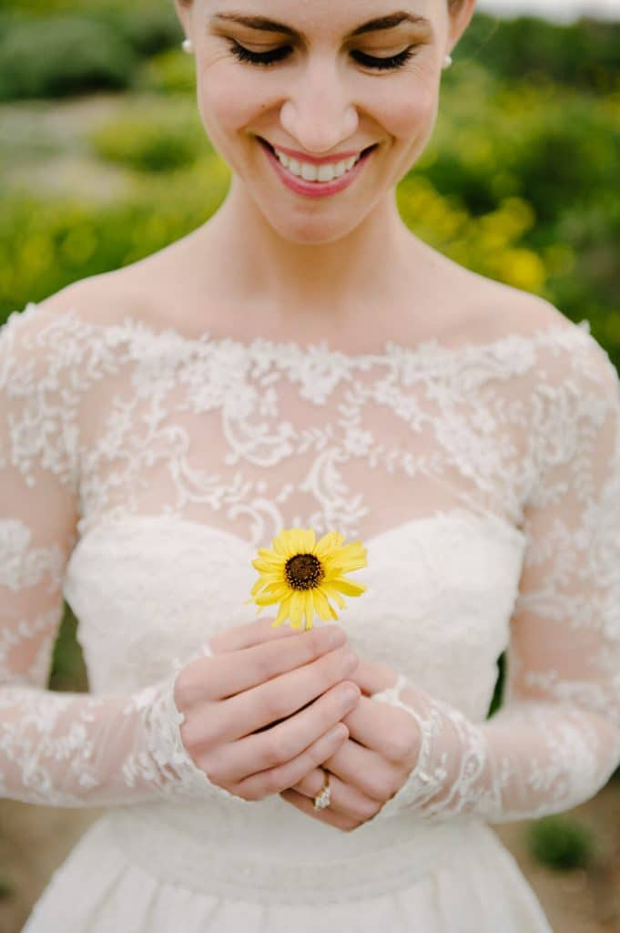 bride in gown with long train and lace sleeves holding yellow wildflower poses at scripps coastal reserve