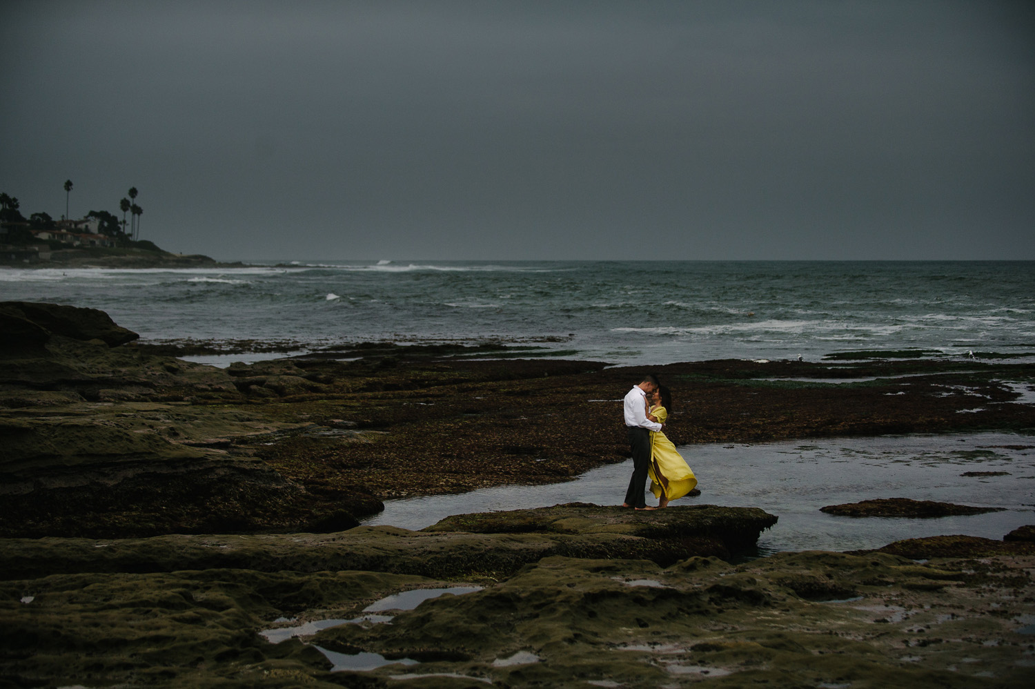 woman in yellow dress embraces fiancee on rocks at marine street beach in la jolla engagement photo