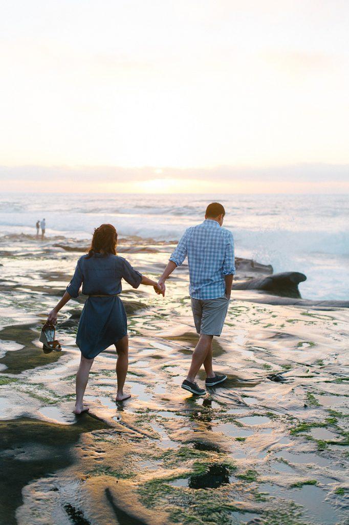 couple walk holding hands tidepools sunset la jolla engagement photo
