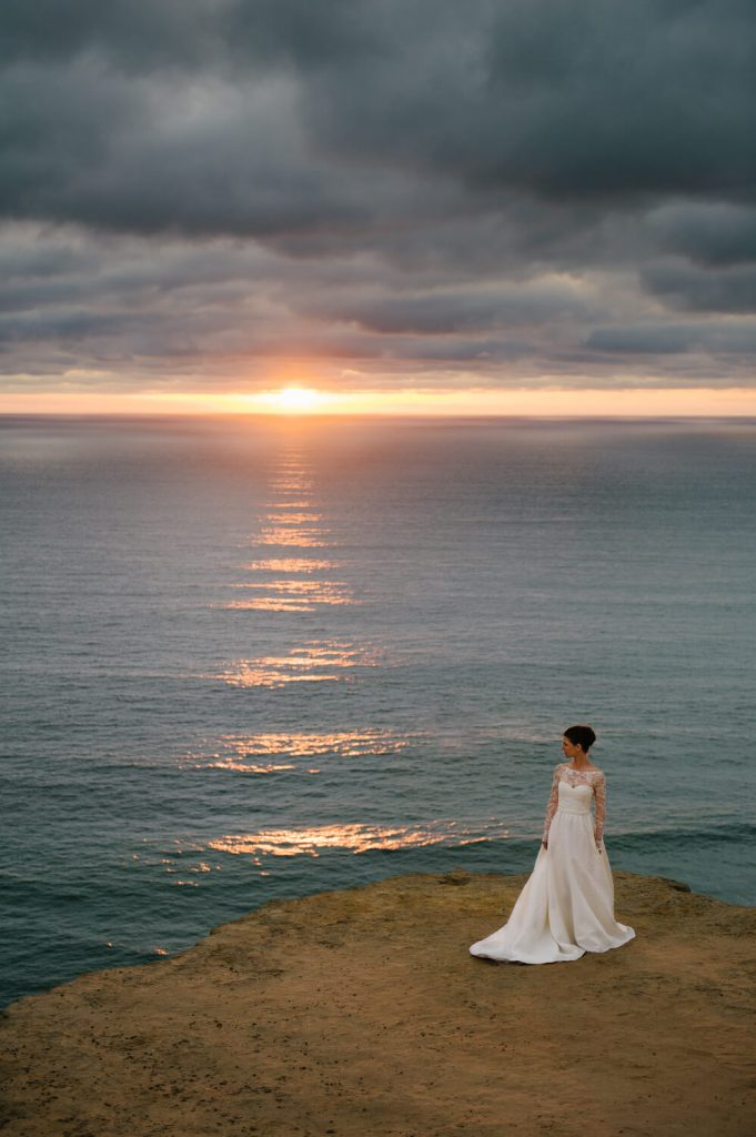 bride in gown with long train and lace sleeves poses at scripps coastal reserve at sunset with dark clouds
