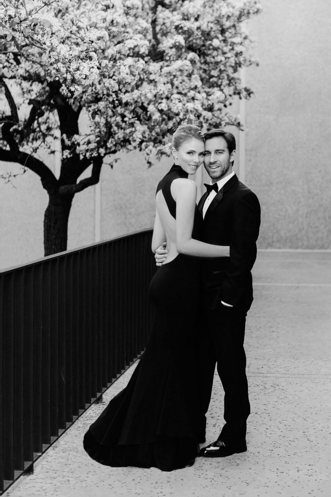 couple in formalwear pose near flowering tree and black railing balboa park classic engagement photo