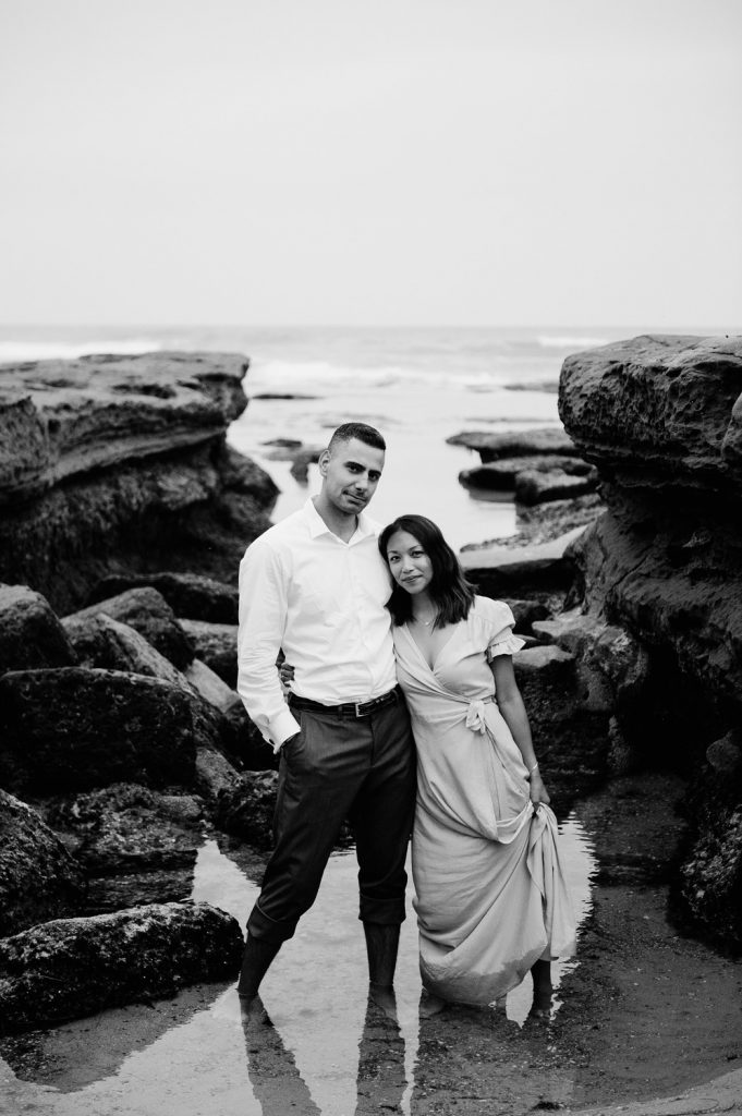 couple wade in water near rocks at marine street engagement photo in la jolla