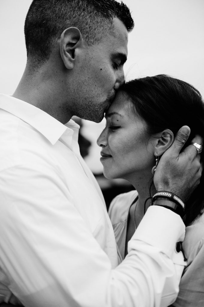 man kisses fiancees head on marine street beach la jolla engagement photo