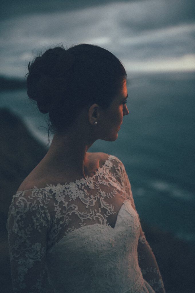 bride in gown with long train and lace sleeves poses at scripps coastal reserve at sunset