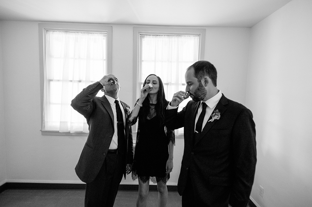groom and siblings drink tequila shot before north chapel ceremony point loma